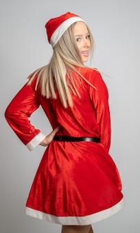 Jonge blonde vrouw in een miss santa claus-kostuum draaien en terugkijken