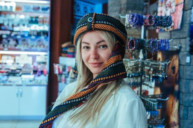 Jonge blonde vrouw in een souvenirwinkel in cappadocië die een hoofdtooi probeert