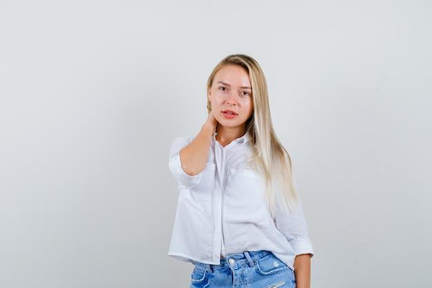 Jonge blonde vrouw in een wit overhemd