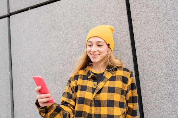 Jonge blonde vrouw in geruite overhemd en gele hoed