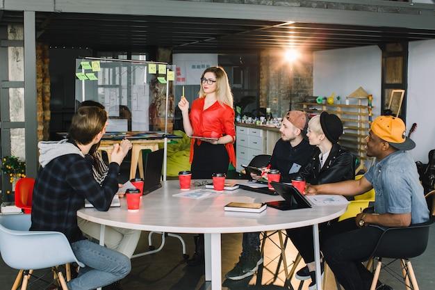 Jonge blonde vrouw in glazen die zich bij glasmuur bevinden in een vergadering met multinationaal team van arbeiders