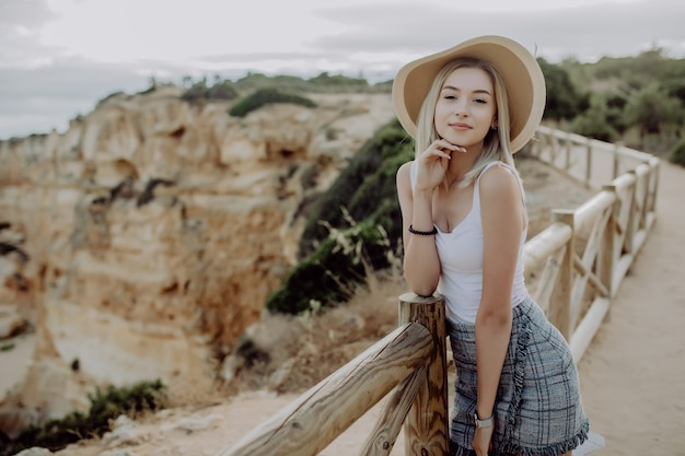 Jonge blonde vrouw in hoed en schattige zomerjurk staande op de steen