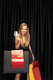 Jonge blonde vrouw in jurk winkelen op zwarte muur.
