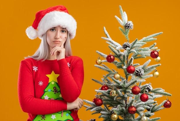 Jonge blonde vrouw in kerst trui en kerstmuts kijken camera verbaasd staande naast een kerstboom op oranje achtergrond