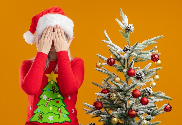 Jonge blonde vrouw in kerstmissweater en santahoed c