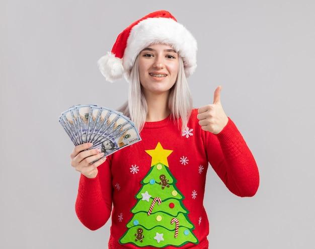 Jonge blonde vrouw in kerstmissweater en santahoed die contant geld houden die met gelukkig gezicht glimlachen die duimen opdagen
