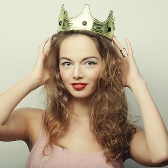 Jonge blonde vrouw in kroon