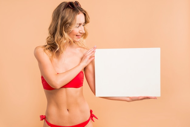 Jonge blonde vrouw in rode bikini die lege raad houdt