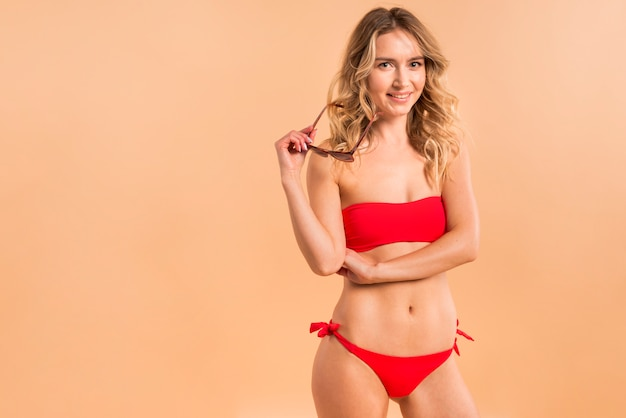 Jonge blonde vrouw in rode bikini op oranje achtergrond