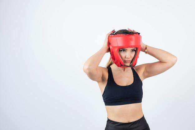 Jonge blonde vrouw in rode bokshelm poseren.