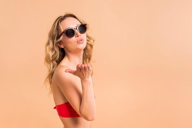 Jonge blonde vrouw in rode bovenkant en zonnebril die luchtkus verzenden