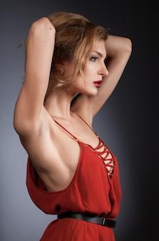 Jonge blonde vrouw in rode jurk op grijze achtergrond