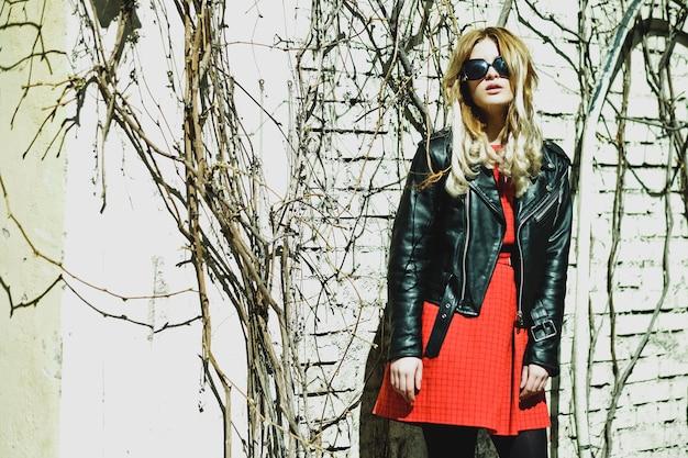 Jonge blonde vrouw in rode jurk poseren in de stad