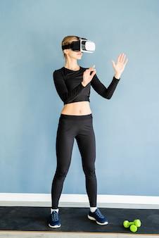 Jonge blonde vrouw in sport kleding vr-bril permanent op fitness mat met behulp van het interactieve menu van vr