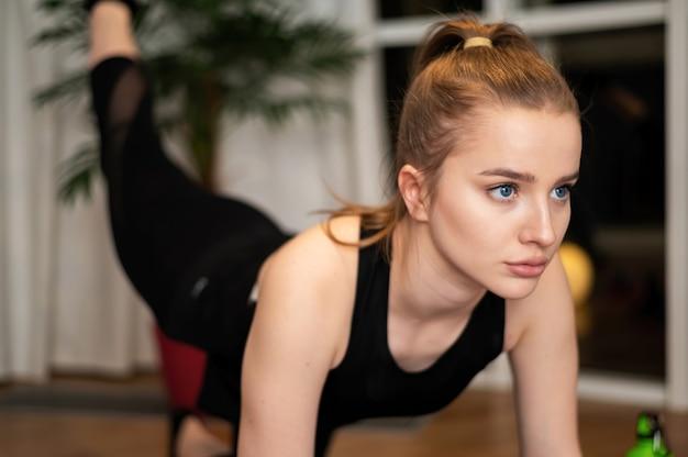 Jonge blonde vrouw in sportkleding doet oefeningen thuis