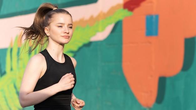 Jonge blonde vrouw in sportkleding draait op de weg bij buiten training, veelkleurige muur op de achtergrond