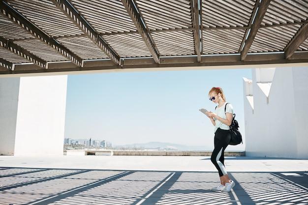 Jonge blonde vrouw in sportkleding luisteren muziek