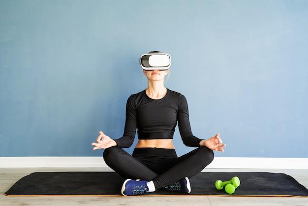Jonge blonde vrouw in sportkleding vr-bril mediteren op fitness mat