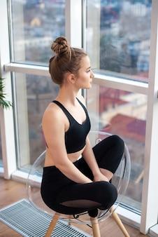 Jonge blonde vrouw in sportkleding zit op een stoel bij de panoramische ramen