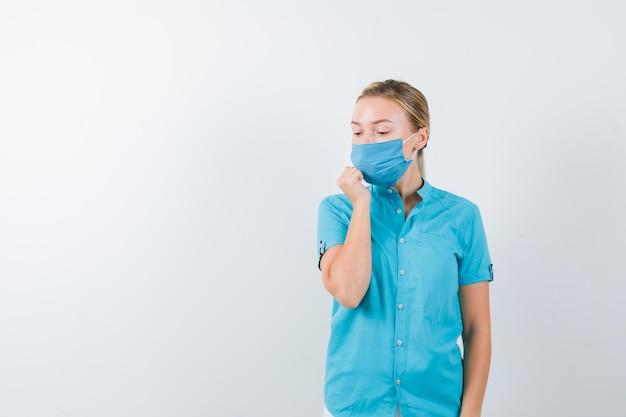 Jonge blonde vrouw in vrijetijdskleding, masker houdt hand in de buurt van mond terwijl ze naar beneden kijkt