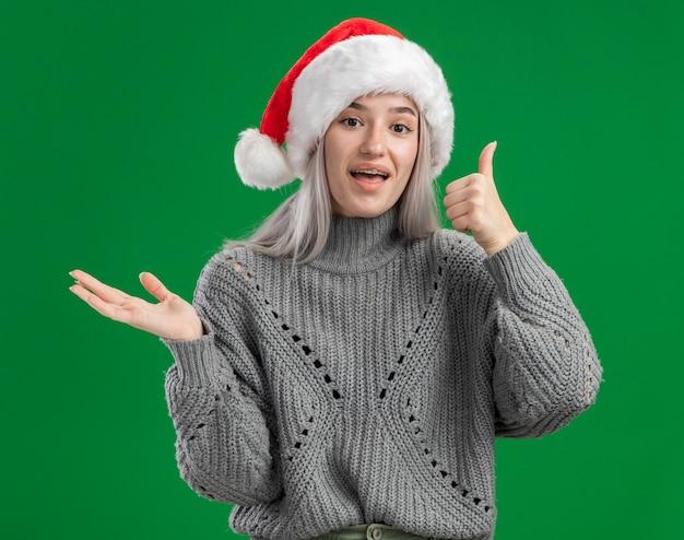 Jonge blonde vrouw in winter trui en kerstmuts kijken camera blij en vrolijk duimen opdagen presenteren kopie ruimte met arm van hand permanent over groene achtergrond