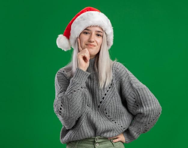 Jonge blonde vrouw in wintertrui en kerstmuts, blij en positief glimlachend zelfverzekerd over groene muur
