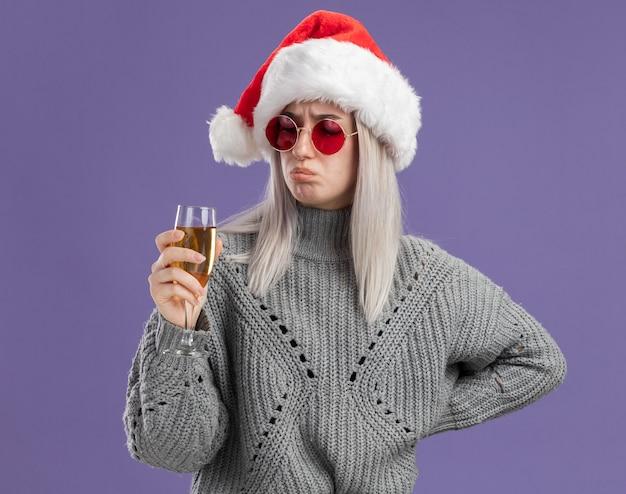 Jonge blonde vrouw in wintertrui en kerstmuts die een glas champagne vasthoudt en er verward en ontevreden naar kijkt terwijl ze over de paarse muur staat