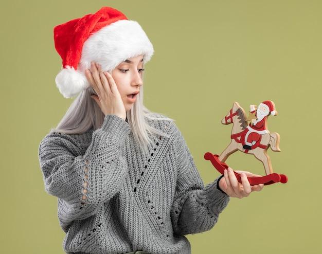 Jonge blonde vrouw in wintertrui en kerstmuts die kerstspeelgoed vasthoudt en er verbaasd naar kijkt terwijl ze over de groene muur staat