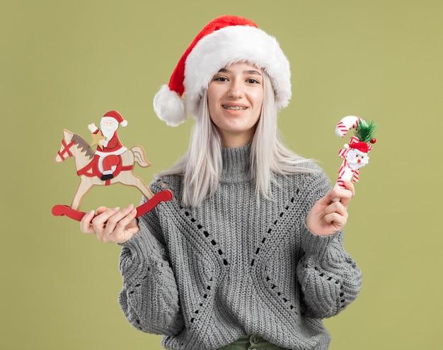 Jonge blonde vrouw in wintertrui en kerstmuts die kerstspeelgoed vasthoudt en vrolijk glimlacht over de groene muur
