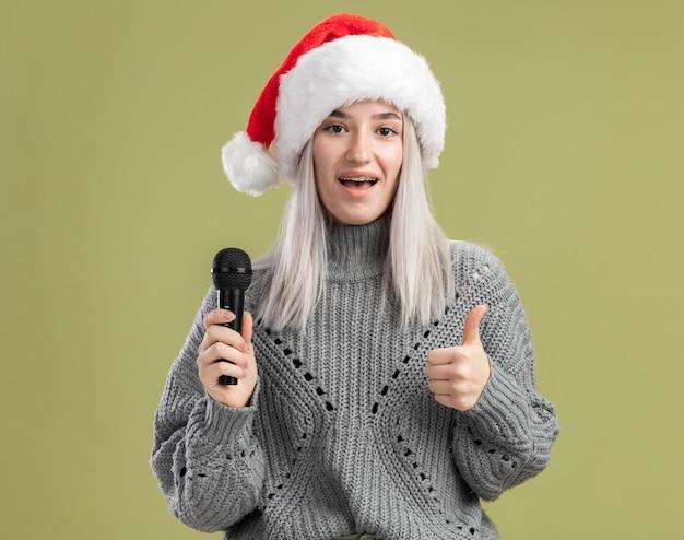 Jonge blonde vrouw in wintertrui en kerstmuts die microfoon vasthoudt met een glimlach op het gezicht die duimen laat zien terwijl ze over de groene muur staan