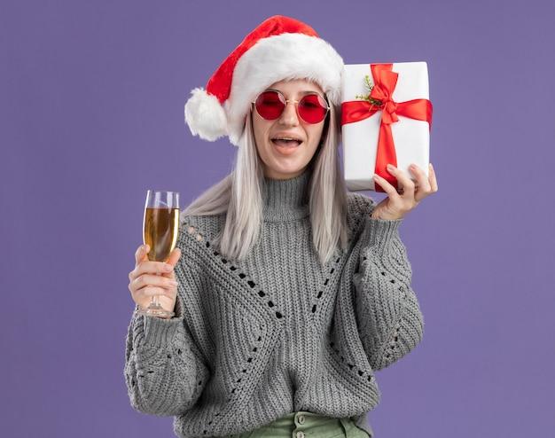 Jonge blonde vrouw in wintertrui en kerstmuts met een cadeautje en een glas champagne blij en opgewonden over de paarse muur