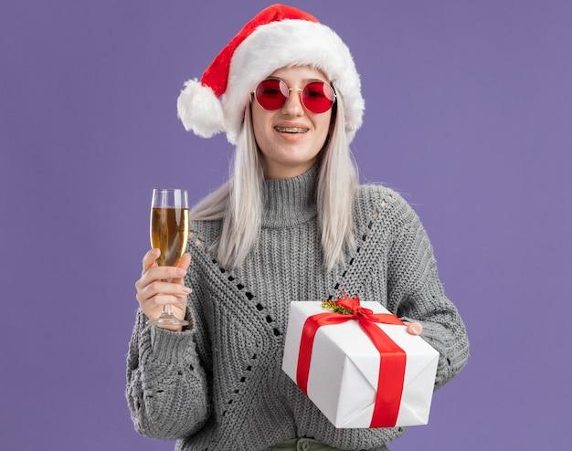 Jonge blonde vrouw in wintertrui en kerstmuts met een cadeautje en een glas champagne met een glimlach op een blij gezicht over een paarse muur