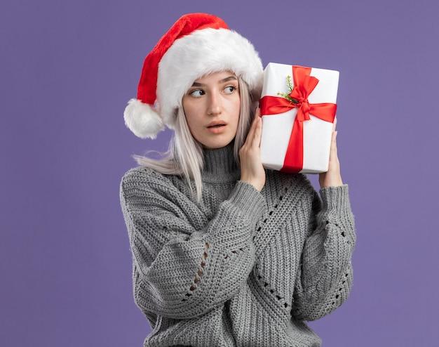 Jonge blonde vrouw in wintertrui en kerstmuts met een cadeautje en kijkt geïntrigeerd over een paarse muur