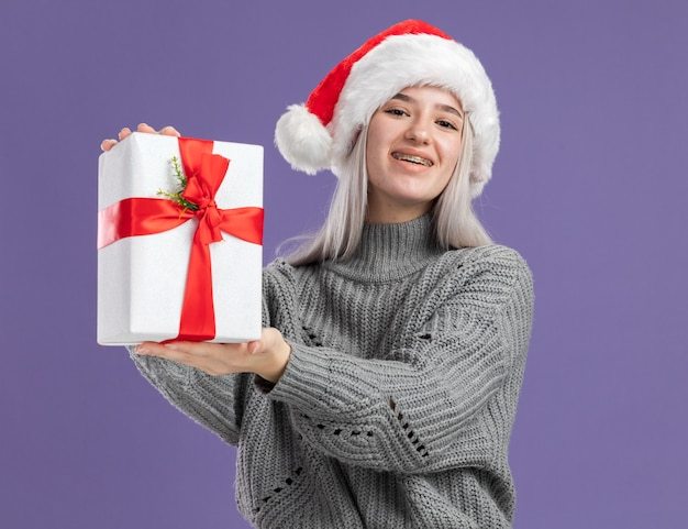 Jonge blonde vrouw in wintertrui en kerstmuts met een cadeautje met een glimlach op een blij gezicht dat over een paarse muur staat