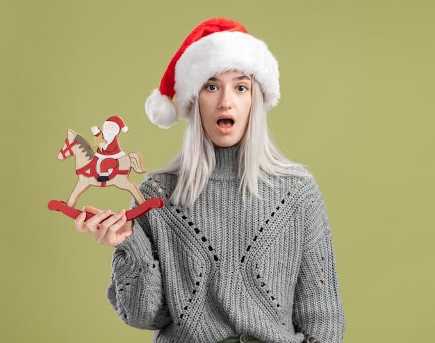 Jonge blonde vrouw in wintertrui en kerstmuts met kerstspeelgoed verrast over groene muur