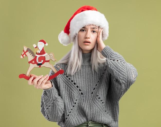 Jonge blonde vrouw in wintertrui en kerstmuts met kerstspeelgoed verward met de hand op haar hoofd die over de groene muur staat green