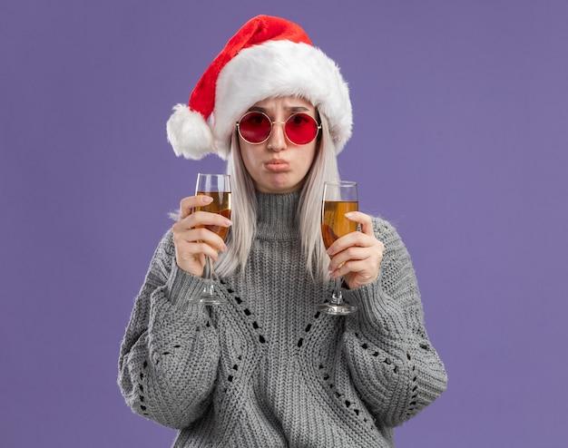 Jonge blonde vrouw in wintertrui en kerstmuts met twee glazen champagne met droevige uitdrukking die lippen tuimelt over paarse muur