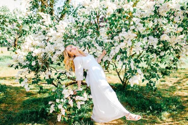 Jonge blonde vrouw in witte jurk poseren in lila struiken,