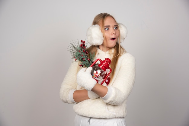 Jonge blonde vrouw in witte outfit met geschenken ergens op zoek.