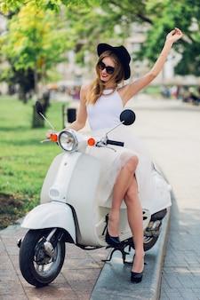 Jonge blonde vrouw in witte tule rok en zwarte hakken zittend op vintage scooter.