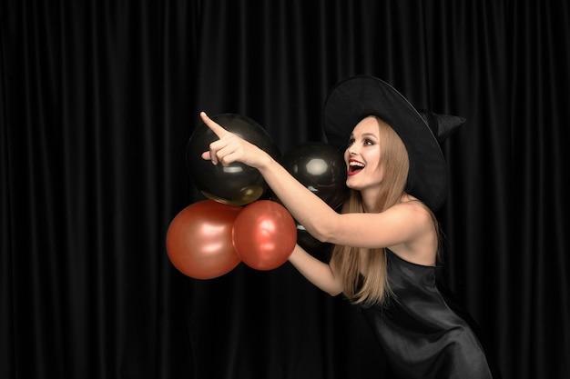 Jonge blonde vrouw in zwarte hoed en kostuum op zwart