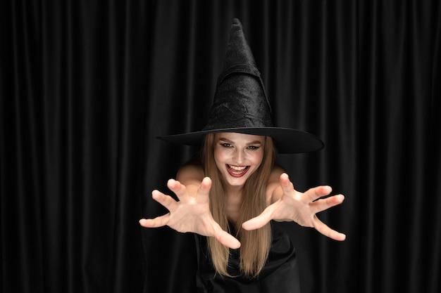 Jonge blonde vrouw in zwarte hoed en kostuum op zwarte achtergrond. aantrekkelijk, sensueel vrouwelijk model. halloween, zwarte vrijdag, cybermaandag, verkoop, herfst