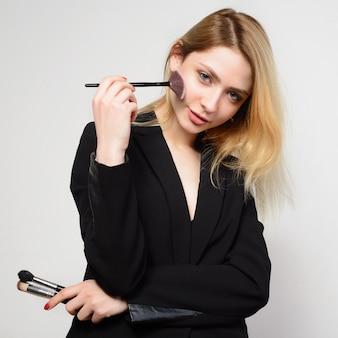 Jonge blonde vrouw in zwarte jas maakt zich een make-up op wit