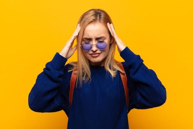 Jonge blonde vrouw kijkt geconcentreerd, attent en geïnspireerd, brainstormend en verbeeldend met de handen op het voorhoofd