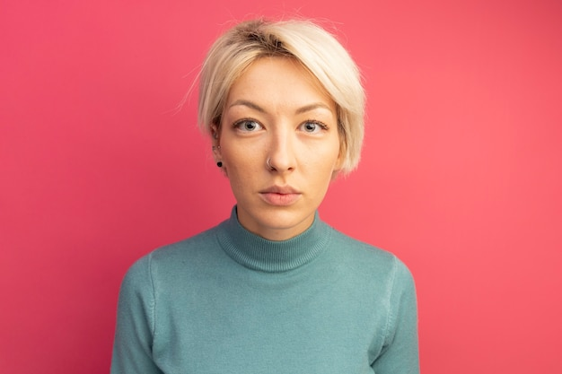 Jonge blonde vrouw kijkt naar de voorkant geïsoleerd op roze wall