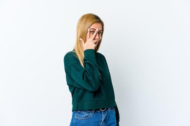 Jonge blonde vrouw knippert door vingers, beschaamd bedekkend gezicht.