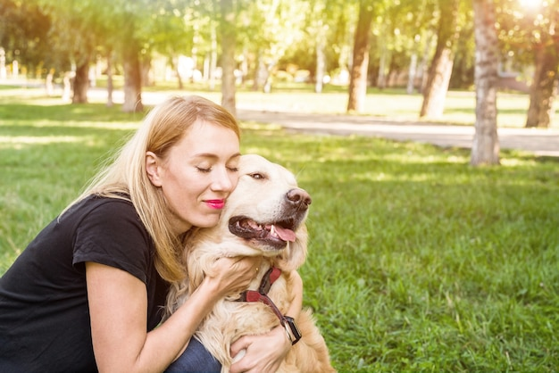 Jonge blonde vrouw knuffelt haar hond. hondenras retriever met een meisje in het park.
