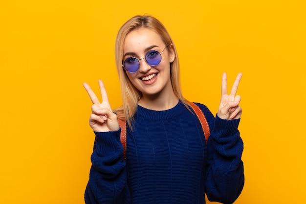 Jonge blonde vrouw lacht en ziet er gelukkig, vriendelijk en tevreden uit, gebarend overwinning of vrede met beide handen