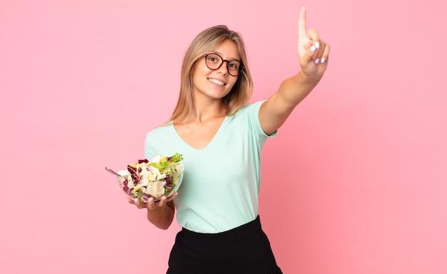 Jonge blonde vrouw lacht en ziet er vriendelijk uit, toont nummer één en houdt een salade vast
