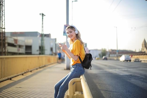 Jonge blonde vrouw leunend op een brughek en sms't op haar telefoon terwijl ze naar muziek luistert